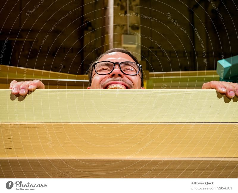 Young man looking over a barrier Interior shot 1 Person Artificial light Portrait photograph Forward Looking into the camera Eyeglasses Fence Barrier