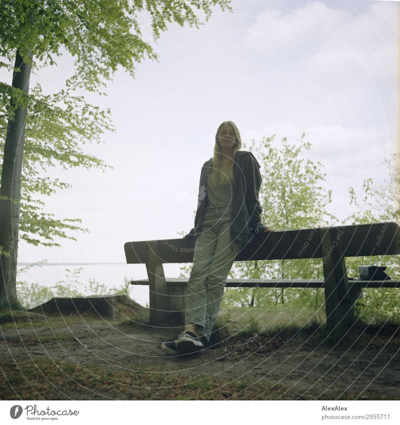 Young woman leaning on a park bench at the Baltic Sea in the forest Joy Beautiful Harmonious Well-being Youth (Young adults) 18 - 30 years Adults Nature