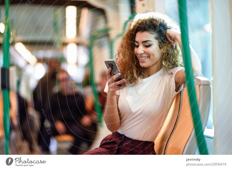 Arab woman inside subway train looking at her smartphone Lifestyle Happy Beautiful Hair and hairstyles Vacation & Travel Tourism Trip Telephone PDA Human being