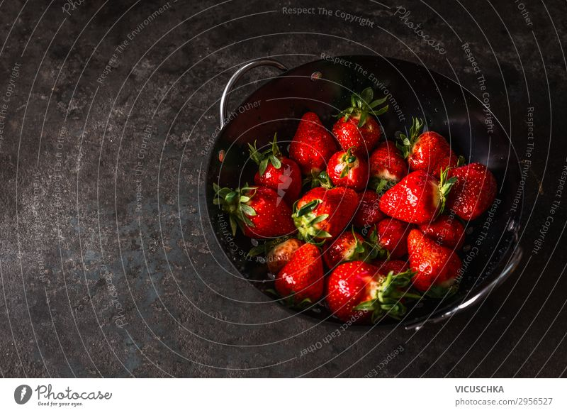 Tasty strawberries in black colander bowl on dark rustic kitchen table. Copy space. Seasonal organic food. Healthy eating and cooking tasty copy space seasonal