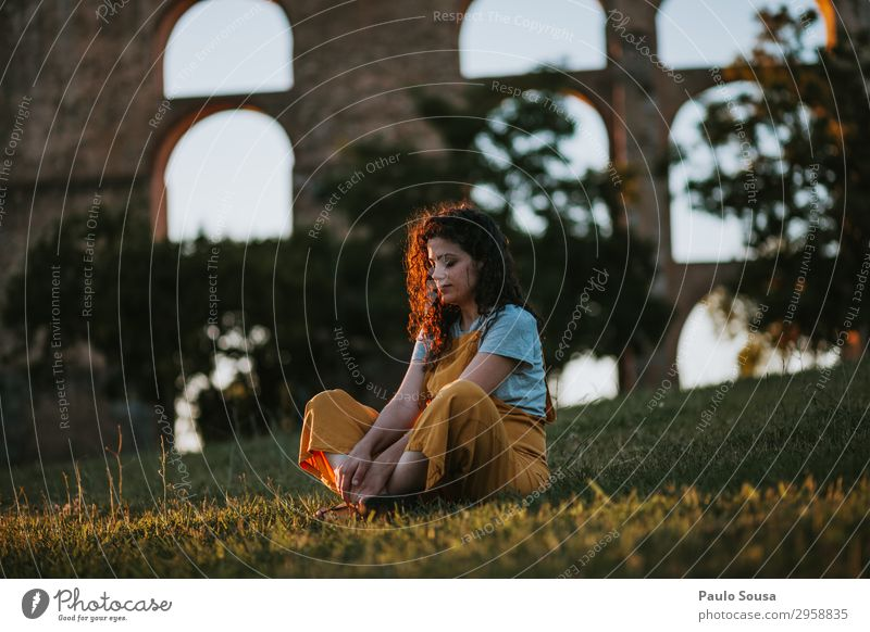 Young woman resting at sunset Lifestyle Well-being Relaxation Meditation Human being Feminine Youth (Young adults) 1 18 - 30 years Adults Nature Summer Park
