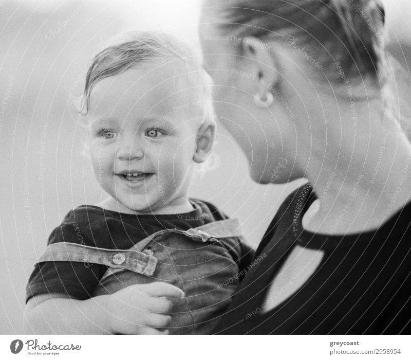 Black and white shot of young mother carrying and looking at joyful one year baby girl with love. Happy motherhood Style Joy Child Human being Baby Woman Adults