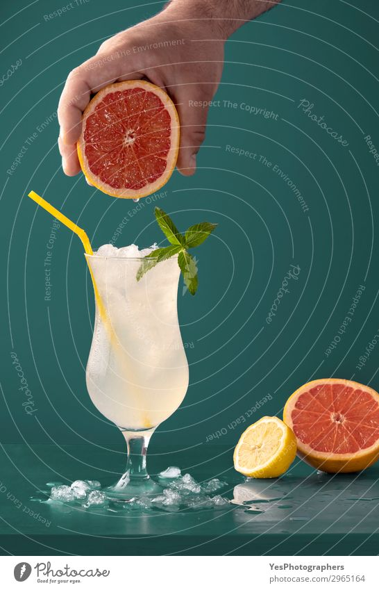 Lemonade cold drink with grapefruit aroma Fruit Diet Beverage Cold drink Juice Summer Fresh Juicy Yellow Green Aromatic Blue background citrus Cocktail