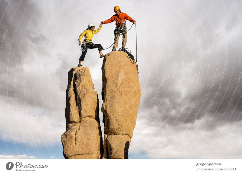 Conquering the summit. Human being Adults Success Adventure Peak Climbing Fear of heights Brave Storm Balance Teamwork Partner Top Self-confident Grasp
