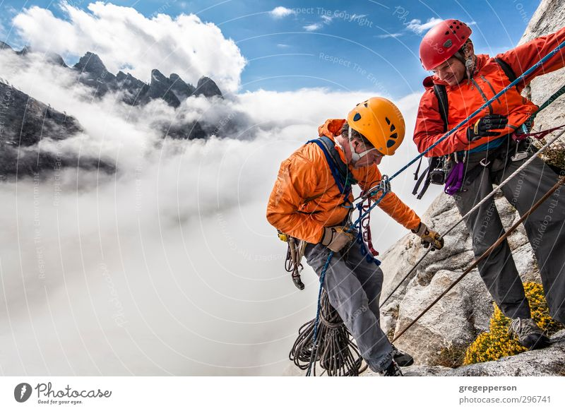 Team of climbers rappelling. Human being Man Clouds Adults Adventure Climbing Fear of heights Brave Storm Balance Teamwork Top Self-confident Grasp Effort
