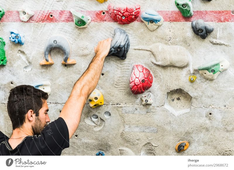 Man practicing rock climbing on artificial wall indoors. Lifestyle Joy Leisure and hobbies Sports Climbing Mountaineering Masculine Young man