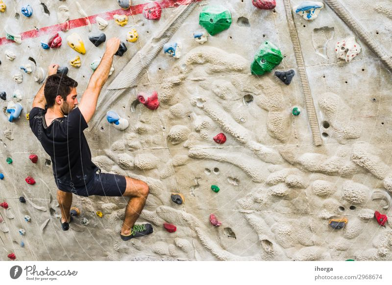Man practicing rock climbing on artificial wall indoors. Active lifestyle and bouldering concept. active black chalk challenge clambering cliff climber