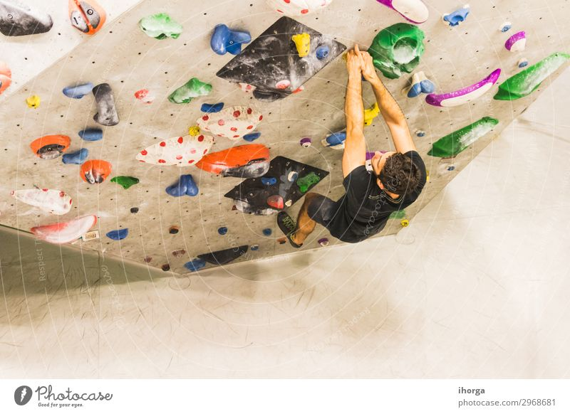 Man practicing rock climbing on artificial wall indoors. Lifestyle Joy Leisure and hobbies Sports Climbing Mountaineering Hiking Adults 1 Human being