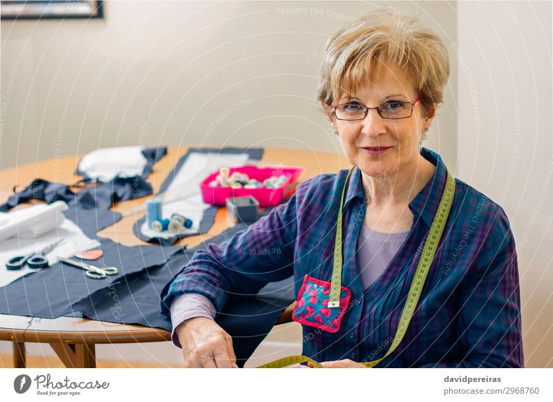 Senior dressmaker posing with sewing materials Woman Human being Old Lifestyle Adults Business Copy Space Fashion Leisure and hobbies Smiling Table Authentic