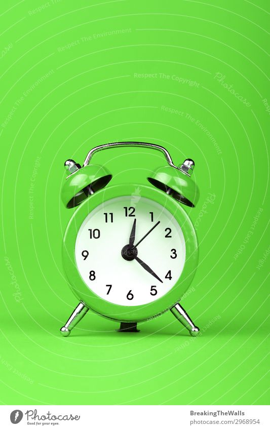 Close up one alarm clock over green background Paper Clock Clock face Clock hand Alarm clock Metal Green timing Period of time Retro Colour photo Multicoloured