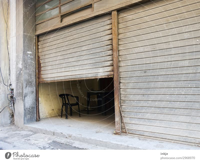 Cuban lunch break Deserted Gate Garage Garage door Disk Main gate Chair Old Authentic Dark Simple Brown Gray Half Closed Open Derelict Dusty Colour photo