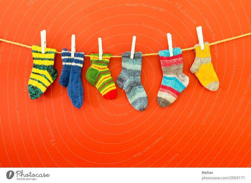 Colourful socks on a clothesline on a red background Style Design Winter Fashion Fresh Retro Warmth Soft Blue Multicoloured Green Red White Diligent Cleanliness