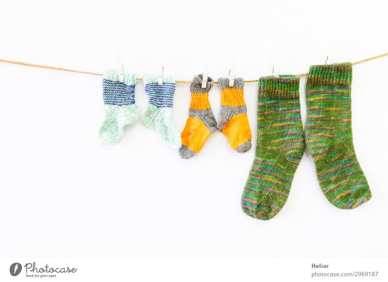 Colourful socks on a clothesline on a white background Style Design Handcrafts Knit Winter Fashion Fresh Retro Warmth Soft Yellow Green White Orderliness