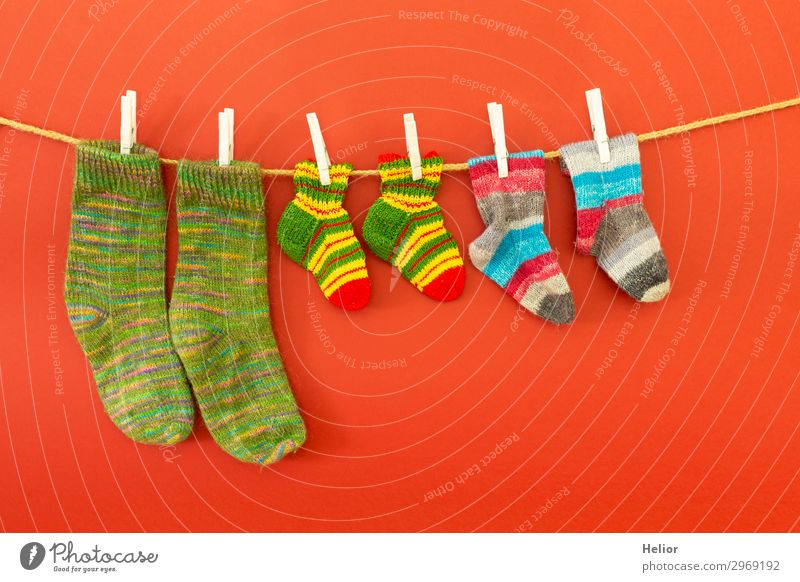Colourful socks on a clothesline on a red background Style Design Handcrafts Knit Winter Fashion Fresh Retro Dry Warmth Soft Blue Multicoloured Green Red