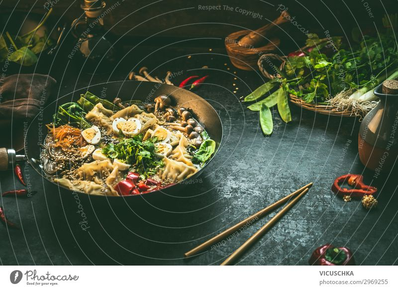 Asian food background with wok pan with vegetarian  korean hot pot and chopsticks on dark rustic kitchen table background, top view. Copy space. asian