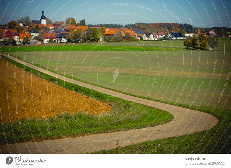 My way which curved through a meadow divided, to a small town in Franconia leads. In the background the village, houses and the church. Joy Life Harmonious