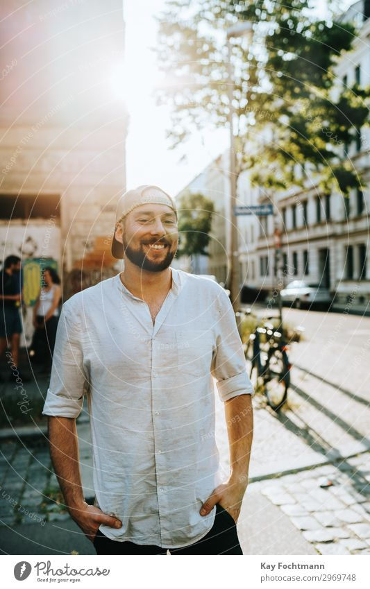 smiling bearded man in summertime attractive baseball cap casual caucasian cheerful citylife confident cool emotion expression face fashion friendly grinning