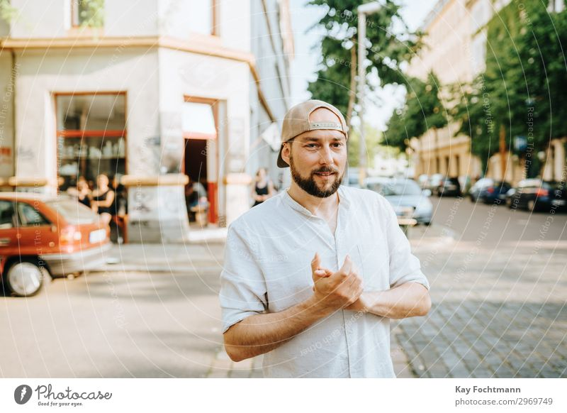 man wearing basecap standing on the street attractive baseball beard bearded casual caucasian cheerful citylife confident cool emotion expression face fashion