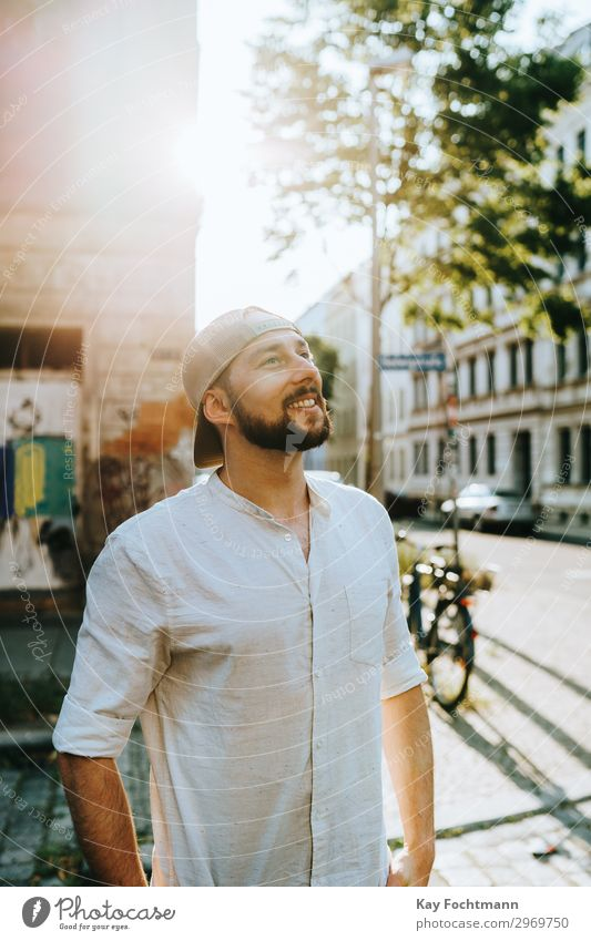 man standing on the street in summer time attractive baseball beard bearded cap casual caucasian cheerful citylife confident cool emotion expression face