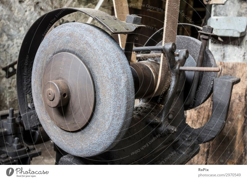 Historic grindstone in the toolshop of a blacksmith. Old Stone Work and employment Metal Retro Technology Industry Construction site Tradition Profession