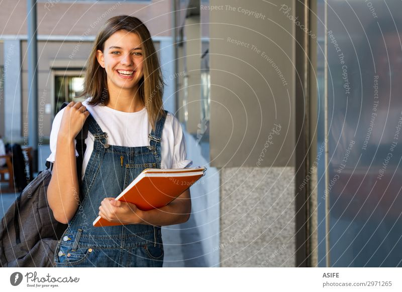 Smiling student girl at the school entrance Lifestyle Happy Beautiful School Academic studies Woman Adults Youth (Young adults) Brunette Laughter Stand Cute