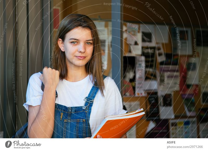 Beautiful student girl at the school entrance Lifestyle Happy School Academic studies Woman Adults Youth (Young adults) Brunette Smiling Stand Cute teenager