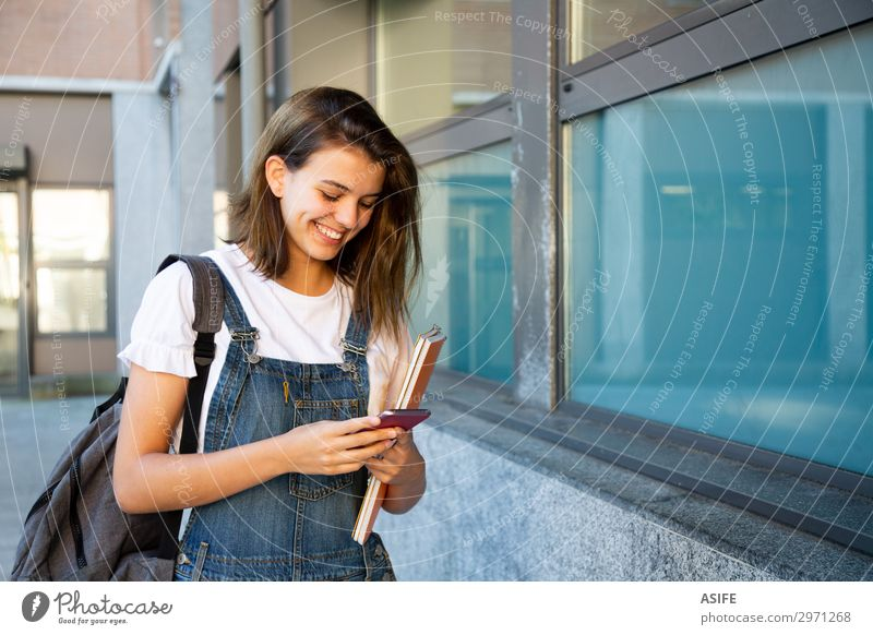 Happy student girl using smart phone at the school corridor Lifestyle Beautiful School Academic studies Telephone PDA Technology Woman Adults