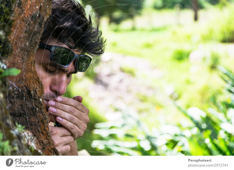 Young man lighting a cigar behind a tree in a forest Alcoholic drinks Lifestyle Luxury Face Relaxation Human being Masculine Man Adults Tree Park Forest