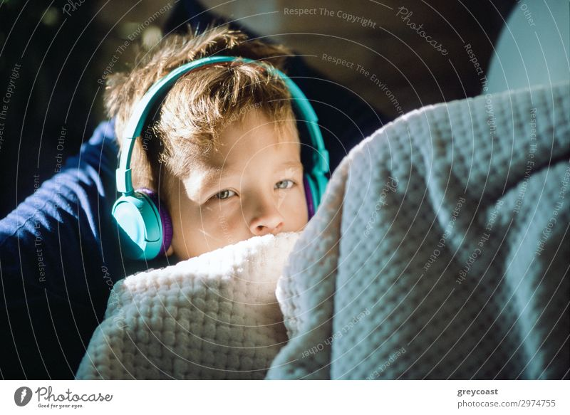 Listening to the music Relaxation Music Headset Boy (child) glance Headphones earpieces blanket Rest leasure sunshine Pillow film film photography Caucasian