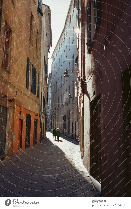 A narrow street between old italian buildings, with a thin sunlight corridor and two human figures far away Human being Town Building Pedestrian Street Historic
