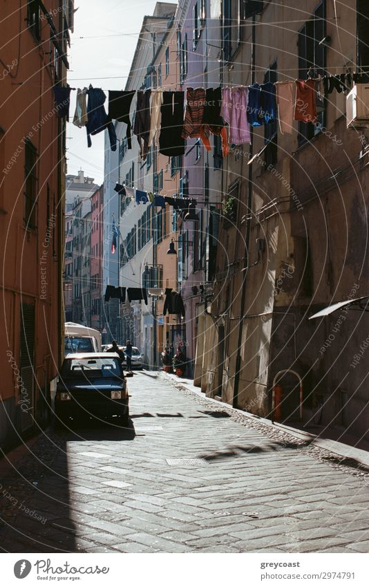 A sunlit authentic narrow Naples street with clothes, hanging on a rope, stretched across the street Lifestyle Rope Street Clothing Authentic Napoli Sunlit