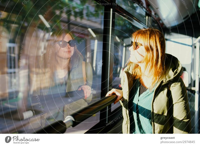 A young red-haired woman in sun glasses looking at her reflection in a bus window Vacation & Travel Trip City trip Human being Young woman Youth (Young adults)