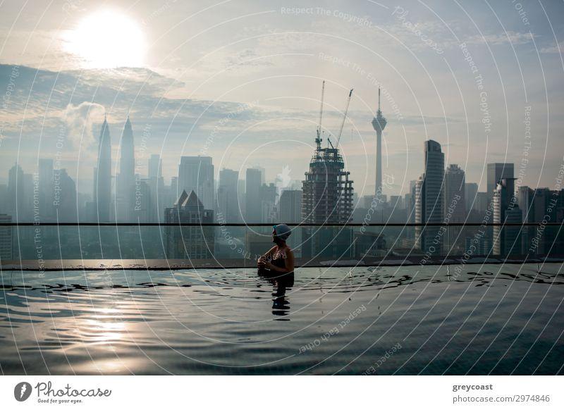 Woman enjoying cityscape of Kuala Lumpur from rooftop swimming pool. Urban scene with skyscrapers, Petronas Tower and Kuala Lumpur Tower, Malaysia Luxury