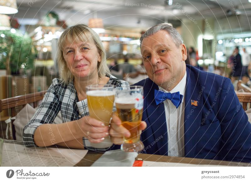 A portrait of a middle aged couple sitting at the table close to each other. Man is wearing a blue jacket and a bright blue bow tie. A woman is in a checkered shirt. Both of them are raising glasses of beer and smiling