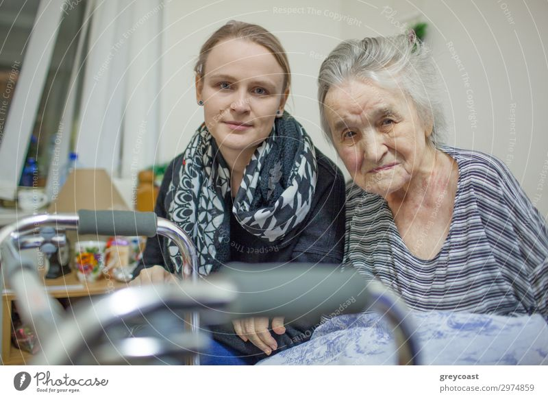 A portrait of a young fair haired woman sitting close to the elderly lady whose hand is on her arm. Both of them are slightly smiling Human being Feminine
