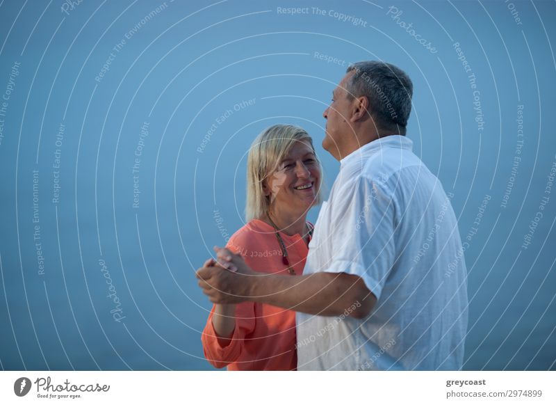 A middle-aged couple dances slightly in front of the blue sky turning into sea Leisure and hobbies Vacation & Travel Trip Ocean Dance Human being Masculine
