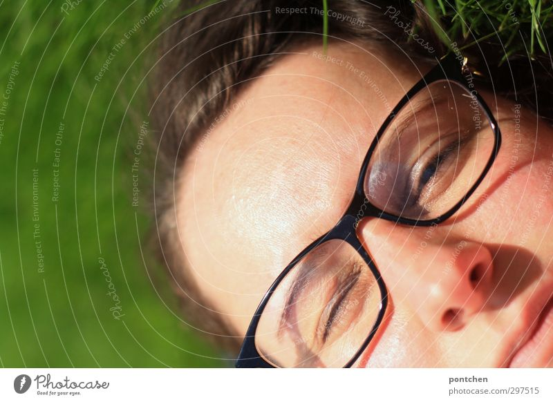 Face of a woman with glasses in the grass. Eyes half closed. Blinking in the sunlight. Recovering and relaxing Feminine Young woman Youth (Young adults) Woman