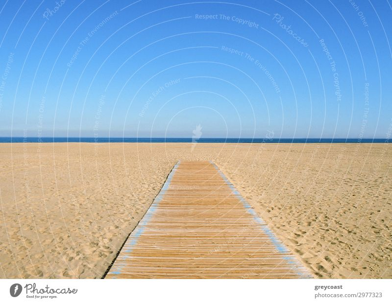 A yellow-blue picture, where the blue half is sky and the yellow half is sand and a wooden path on it. A thin dark blue line of sea in the middle Sun Beach