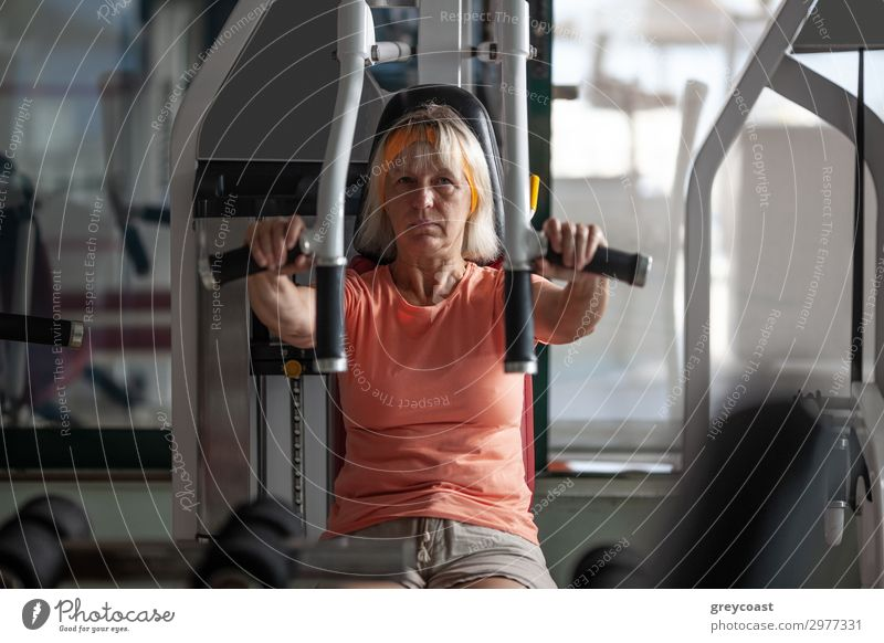 An older woman practices exercises on a fitness trainer Sports Fitness Sports Training Sporting Complex Human being Feminine Woman Adults 1 45 - 60 years Blonde
