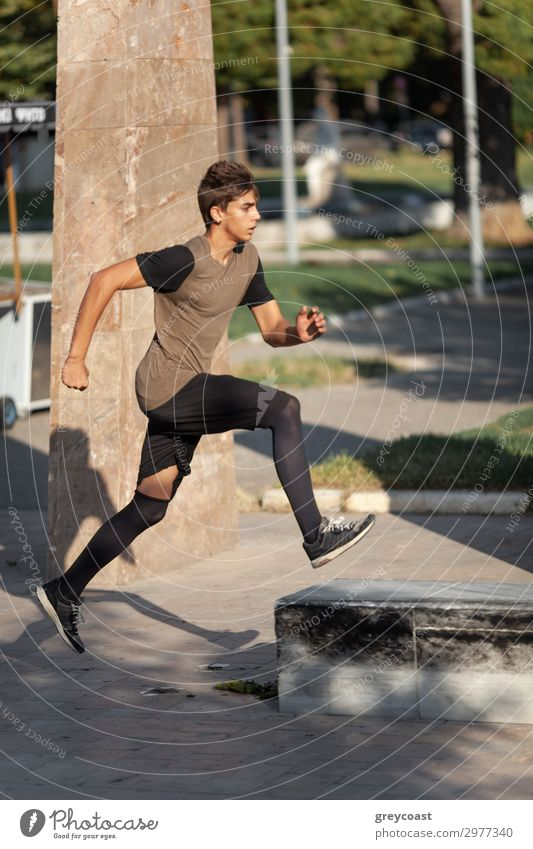 A teenage boy goes in for parkour in a city park Sports Track and Field Jogging Human being Masculine Young man Youth (Young adults) 1 13 - 18 years T-shirt