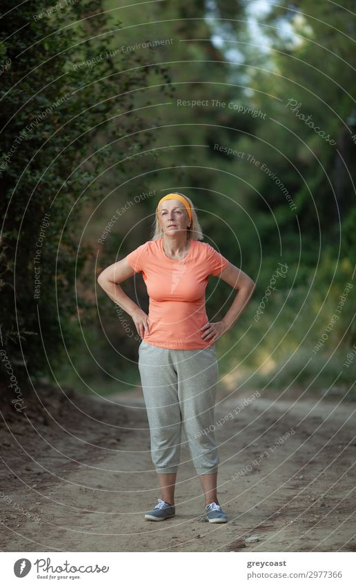 A middle-aged woman is standing on a park path with hands on her hips, tired after a jog Sports Human being Feminine Woman Adults Female senior 1 45 - 60 years