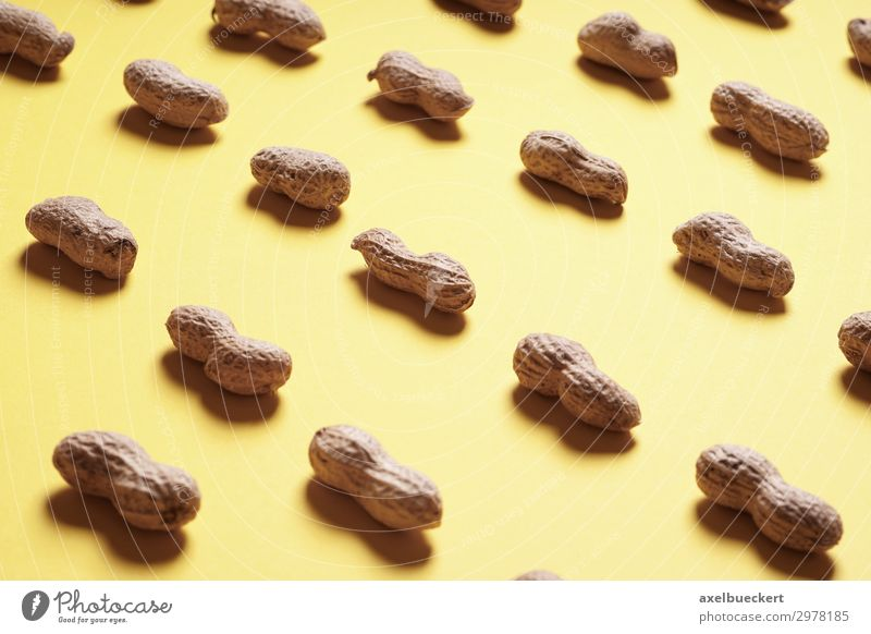 Peanut arrangement on yellow background Food Nutrition Design Healthy Eating Yellow Arranged Vitamin Snack Protein Background picture Still Life Nutshell Row