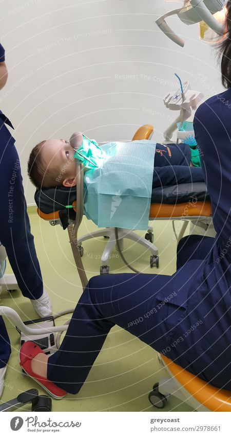 A fragment of a dental room with a kid, lying on a dental chair, and a part of his doctors figure Medical treatment Child Work and employment Doctor Human being