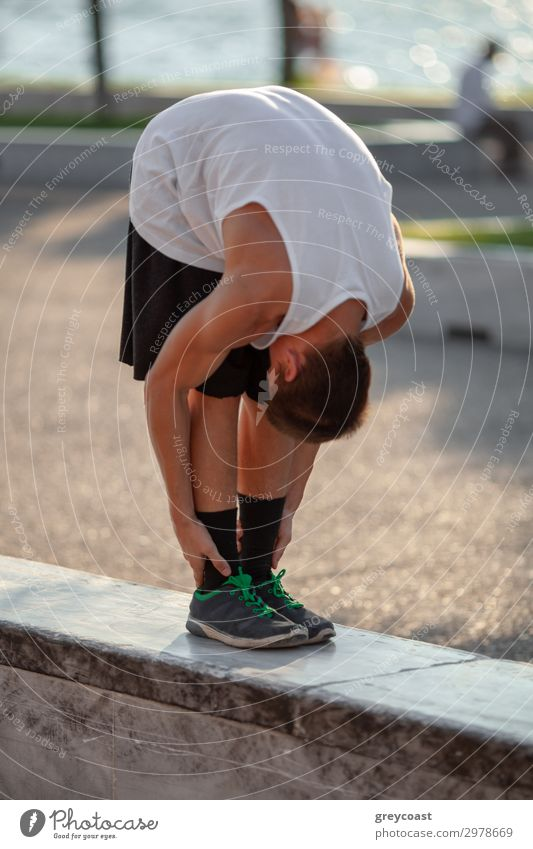 A teenage boy stretches down, pulling his head to his knees, outdoors Sports Track and Field Sportsperson Yoga Masculine Young man Youth (Young adults) 1