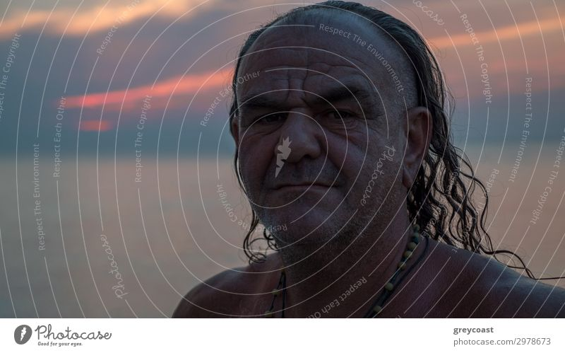 A portrait of a middle-aged man with long hair and a couple of necklaces on his naked chest Lifestyle Summer vacation Masculine Man Adults Male senior