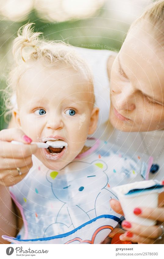 A baby girl is spoon fed with yogurt by her mother Yoghurt Dessert Eating Spoon Child Human being Feminine Baby Girl Young woman Youth (Young adults) Mother