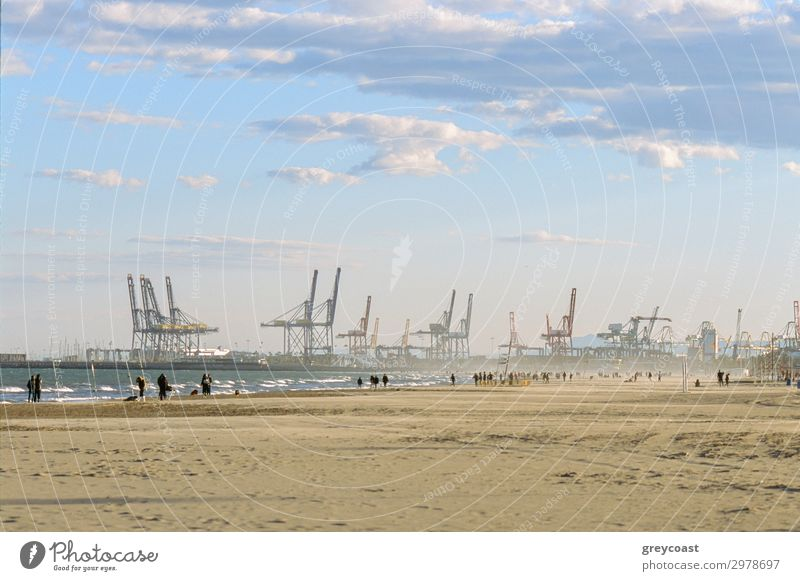 People walking on the beach of Valencia in winter, Spain. Scene with industrial port and container cranes Beach Ocean Industry Sky Waves Coast Inland navigation