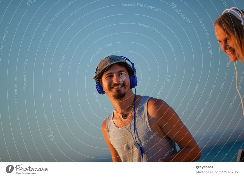 Young man and woman spend time in the open air with headphones on their heads Joy Ocean Music Masculine Feminine Woman Adults Man Friendship