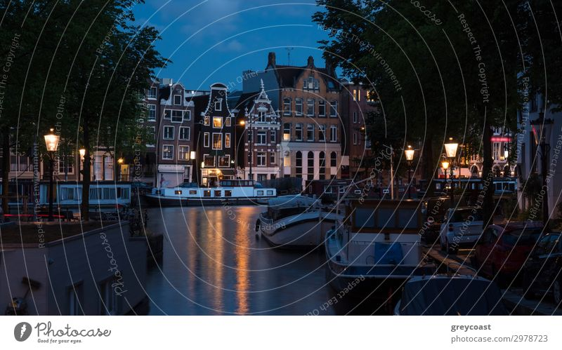 Amsterdam night scene with traditional houses, boats moored along the canal and lit lanterns, Netherlands Vacation & Travel Tourism Sightseeing