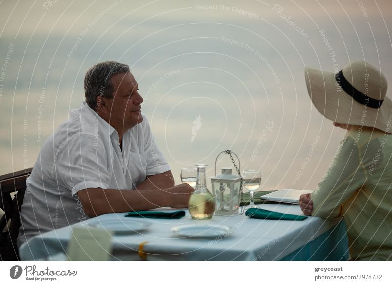 Mature couple having romantic evening. They enjoying the time and looking at each other sitting at the table in waterfront restaurant Dinner Happy Relaxation